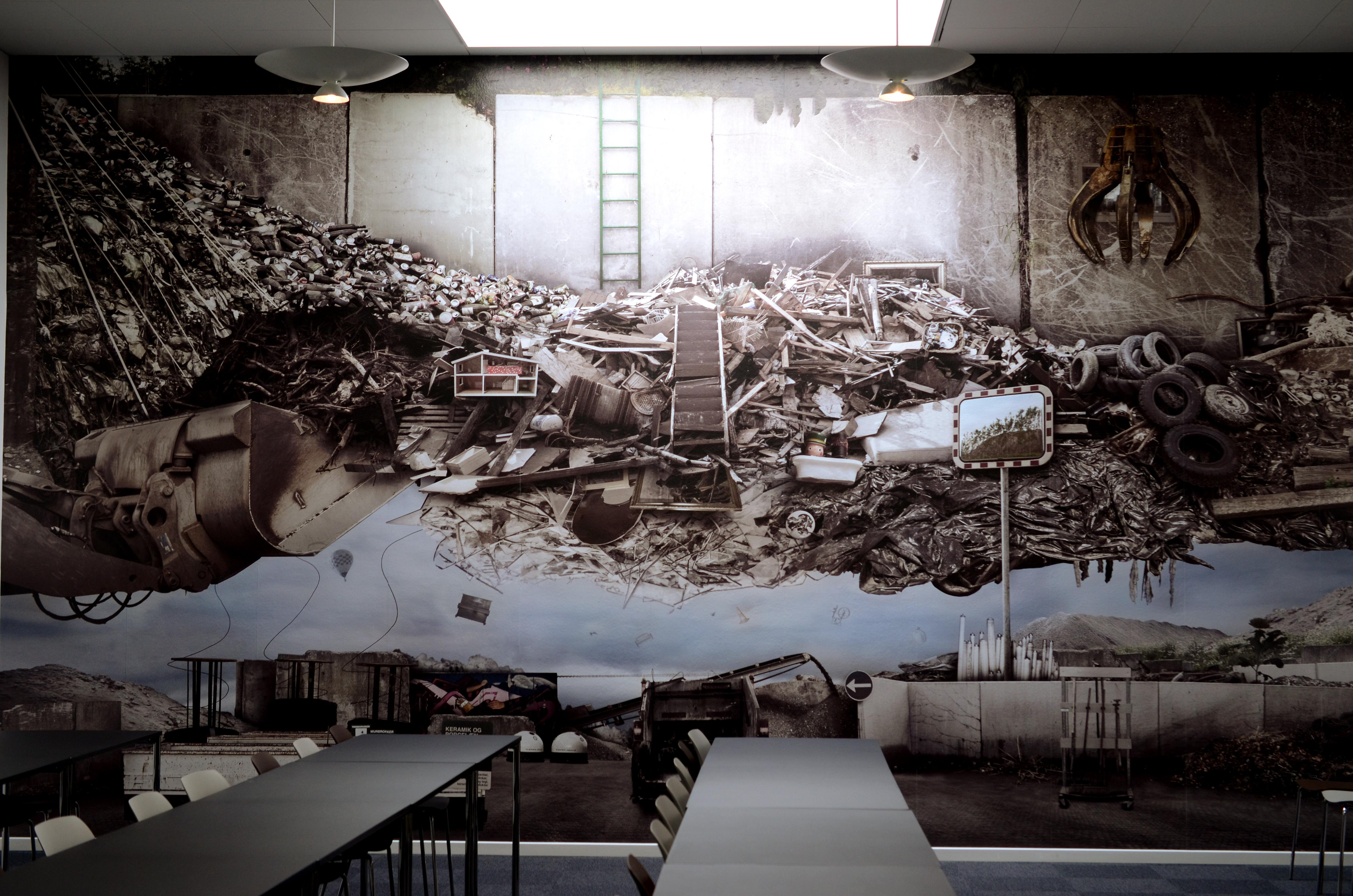 """I det store konferencerum hænger der en stor fotocollage """"Afterlife of stuff"""" lavet af Inger Tranter. Talerstolen er en stabel gamle kufferter på en flytbar bund, der fungerer rigtig fint i det gennemførte hus' helhed."""