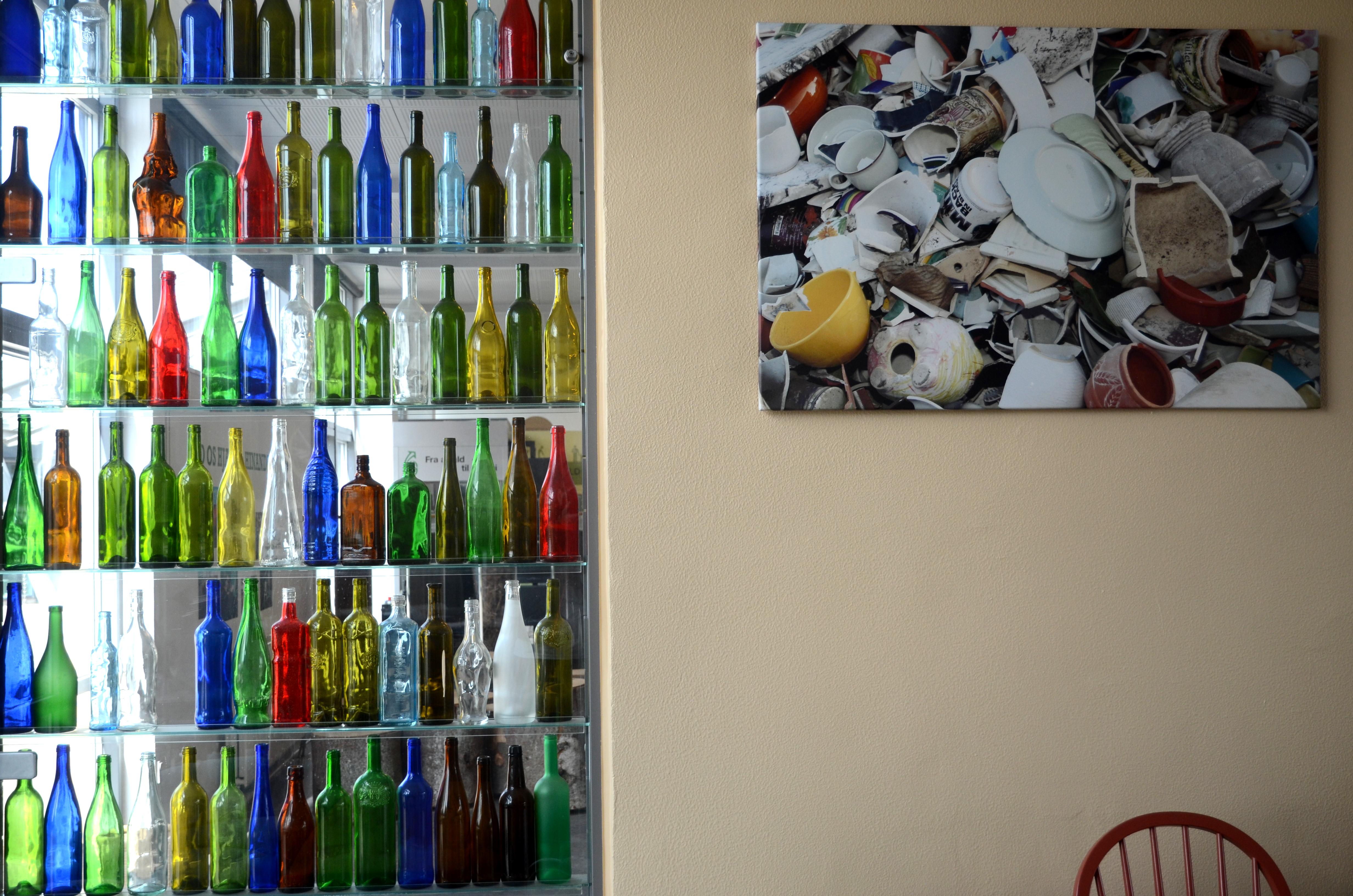 I kantinen hænger der flotte billeder af blandt andet en bunke knust og skåret keramik ved siden af en glasmontre med smukke farvestråelende flasker.